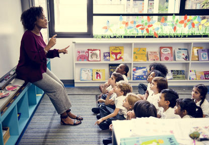 woman in front of a class of children