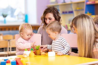 women watching children play with pretend foo