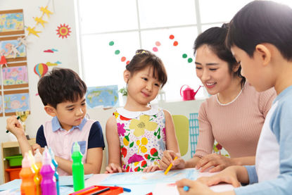 woman working with group of children