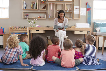 woman reading book to children