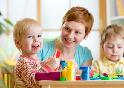 woman watching two young children